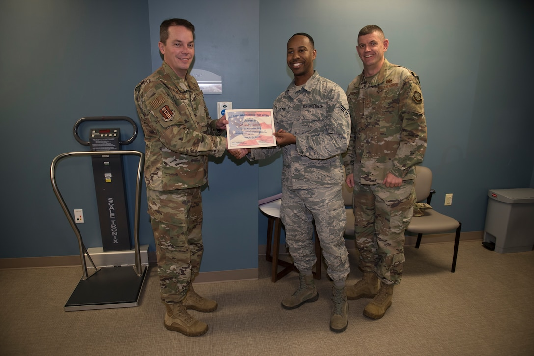U.S. Air Force Senior Airman Andre Hamilton, center, 60th Medical Support Squadron health services management technician, is recognized by Col. Jeffrey Nelson, left, 60th Air Mobility Wing commander, and Chief Master Sgt. Derek Crowder, right, 60th AMW command chief, as Warrior of the Week Nov. 19, 2019, at Travis Air Force Base, California. Hamilton was recognized as the WoW for Nov. 17-23. The program highlights a Travis Airman for his or her outstanding performance. (U.S. Air Force photo by Airman 1st Class Cameron Otte)