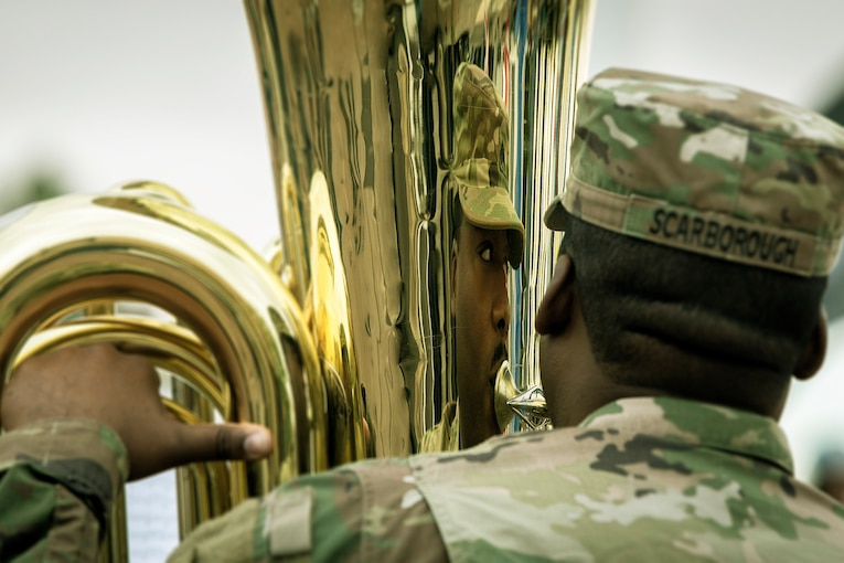 A soldier is reflected in the brass instrument he is playing.