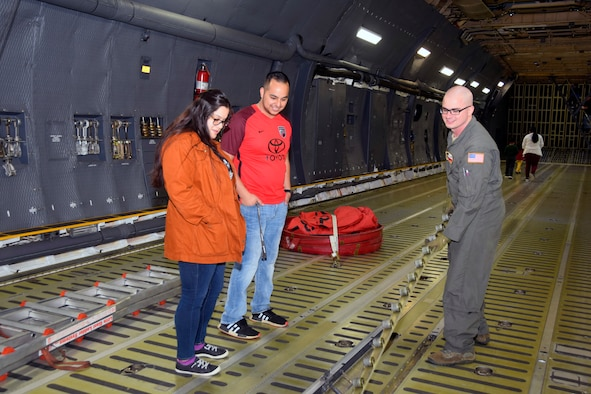 U.S. Air Force Staff Sgt. Michael L. Indo, 68th Airlift Squadron flight engineer, shows Ashley M. Jones and Kevin C. Castillo the inboard logistical rail and roller conveyer while inside a C-5M Super Galaxy aircraft during the Youth Aerospace Expo at Kelly Field, Texas, Nov. 16, 2019.
