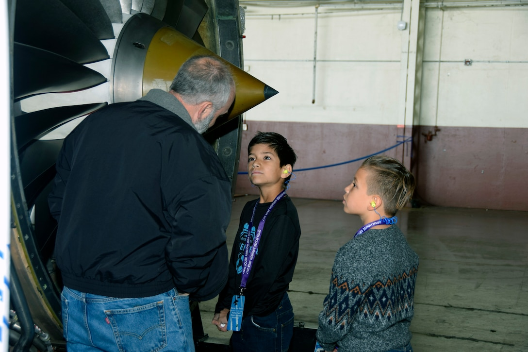 Joshua Shappell and Brodie Alvadel listen to Devin Thompson, a StandardAero employee, talk about engine operation at the Youth Aerospace Expo at Kelly Field, Texas, Nov. 16, 2019.