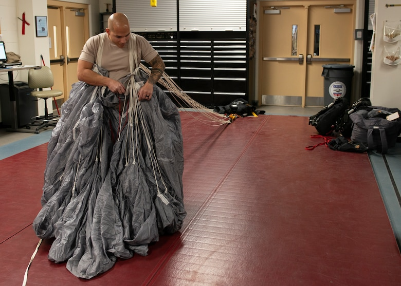 Alaska Air National Guard Tech. Sgt. Eduardo Peguero, 176th Operations Support Squadron aircrew flight equipment technician, packs a parachute at Joint Base Elmendorf-Richardson, Alaska, Nov. 14, 2019. The AFE Guardian Angel Section supports Alaska's rescue mission by preparing parachutes and maintaining the equipment needed to deploy pararescuemen as an emergency response.