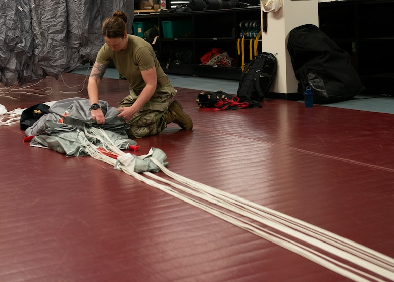 Alaska Air National Guard Staff Sgt. Mel Romero, 176th Operations Support Squadron aircrew flight equipment technician, packs a parachute at Joint Base Elmendorf-Richardson, Alaska, Nov. 14, 2019. The AFE Guardian Angel Section supports Alaska's rescue mission by preparing parachutes and maintaining the equipment needed to deploy pararescuemen as an emergency response.
