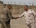 Col. Ali Husayen Abdallah Aljaf, officer-in-charge of Iraq Army Transportation Brigade, shakes hands with U.S. Army Capt. Alfred Vidrio, procurement project officer-in-charge of supply and service of the 108th Sustainment Brigade, at a collection point for tactical and non-tactical vehicles repair parts near Camp Taji, Iraq, Oct. 21, 2019. Task Force Lincoln's divestment is one of the first divestments where the Iraqi military will go through the Iraq Army logistic system that will increase self-sufficiency in transporting spare parts and equipment. (U.S. Army photo by Capt. Karla M. Crayne)