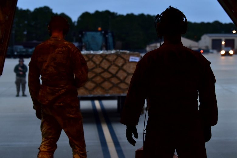 Personnel in uniform operate on an airfield and in an aircraft