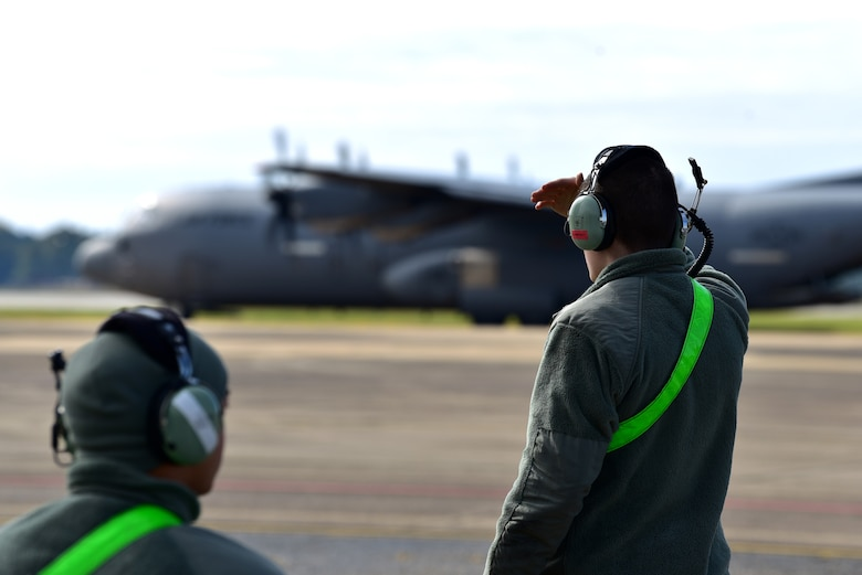 Personnel in uniform operate in and around an aircraft on an airfield