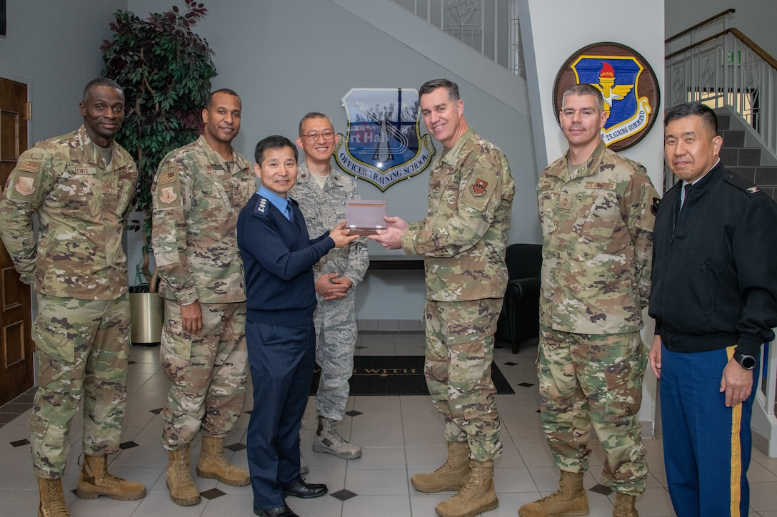 Chaplain, Col. Kwang-Nam Na, Republic of Korea Air Force Chief of Chaplains, and Chaplain, Col. Michael Newton, Air Force Chaplain Corps Chief of Chaplains commandant, extend mutual tokens of appreciation during a visit to Air University Nov. 13-15, 2019, at Maxwell, Air Force Base, Alabama. The visit, as a whole, was held to signify their commitment to strengthening national and functional alliances in support of the Secretary of the Air Force's priorities. Also included in the photo are (left to right) Chief Master Sgt. Gabriel Lewis, Officer Training School superintendent, Col. Peter Bailey, OTS commandant, Chaplain, Maj. Shin Soh, ROKAF translator, Chief Master Sgt. Michael Taylor, AFCCC chief, Chaplain, Col. Samuel Lee, United Nations Command, Combined Forces Command and United States Forces Korea Command Chaplain.