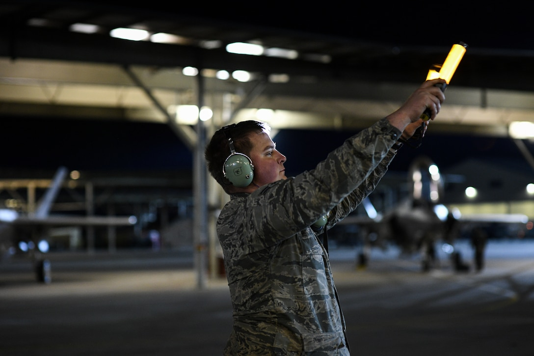 A maintainer marshals an F-35A at Hill Air Force Base, Utah on Nov. 13. 2019. The 34th Fighter Squadron departed Hill for Al Dhafra Air Base, United Arab Emirates, to support the United States Air Force Central Command mission in the MIddle East. The group of deploying Airmen was made up of pilots from the active duty 34th Fighter Squadron and Reserve 466th Fighter Squadron, as well as active duty and Reserve Airmen in the 34th Aircraft Maintenance Unit, and personnel in other support functions. (U.S. Air Force photo by R. Nial Bradshaw)