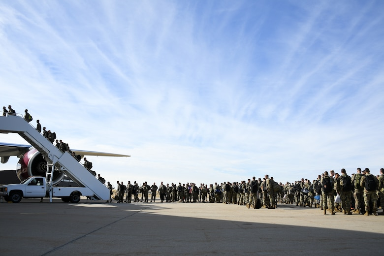 Photo of Airmen boarding a plane.