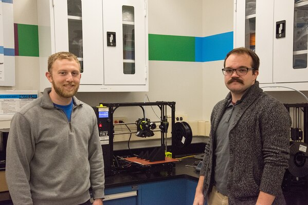 Jacob Aljundi (left) and Ryan Fisher, engineers in the Additive Manufacturing Branch at Naval Surface Warfare Center Carderock Division, stand in front of a 3D printer in Carderock's Manufacturing, Knowledge and Education Lab on Nov. 15, 2019, in West Bethesda, Md. The two engineers travel to different parts of the world training deployed U.S. Marines how to use 3D printers and the associated software and technology. (U.S. Navy photo by Edvin Hernandez/Released)