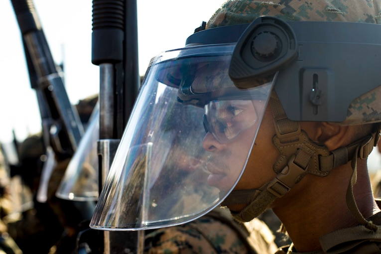 A Marine wears a mask while standing an a line with other Marines.