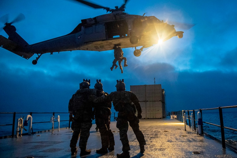 Three Coast Guardsmen look up toward a helicopter as another Coast Guardsman is hoisted up.
