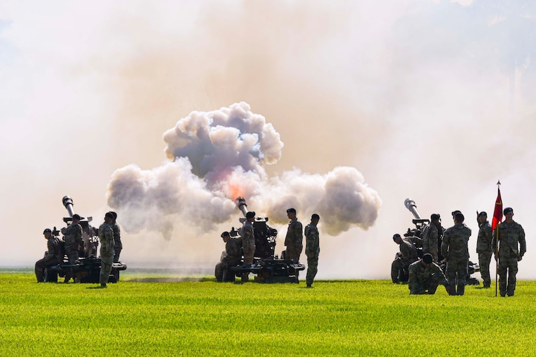 A group of soldiers fire cannons.