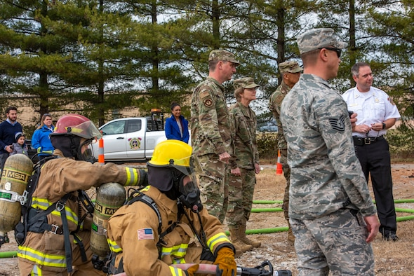 Gen. Maryanne Miller, Air Mobility Command commander, and Chief Master Sgt. Terrence Greene, AMC command chief, visit with 375th Civil Engineer Squadron Fire Protection members during a training exercise at Scott Air Force Base, Ill., Nov. 18, 2019.