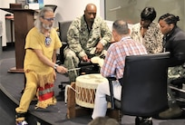 """IMAGE: Virginia Beach, Va. (Nov. 12, 2019) – Joe Rubye, a retired Navy chief petty officer and member of the Jicarilla Apache (Tinde) Nation, sings a pow wow song while four Naval Surface Warfare Dahlgren Division - Dam Neck Activity team members keep a rhythmic beat during an American Indian Heritage Month celebration in Hopper Hall Auditorium. Rubye's drum is named """"Four Itsa Feather"""" (Itsa=Eagle) and it is a family heirloom.  (U.S. Navy Photo by IT1 Justin Owens/Released)"""