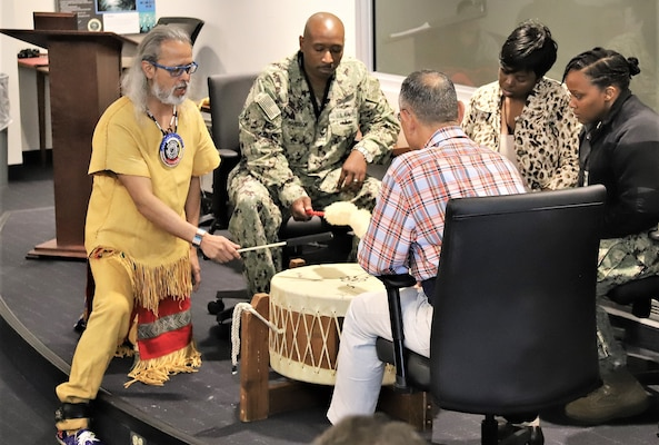 "IMAGE: Virginia Beach, Va. (Nov. 12, 2019) – Joe Rubye, a retired Navy chief petty officer and member of the Jicarilla Apache (Tinde) Nation, sings a pow wow song while four Naval Surface Warfare Dahlgren Division - Dam Neck Activity team members keep a rhythmic beat during an American Indian Heritage Month celebration in Hopper Hall Auditorium. Rubye's drum is named ""Four Itsa Feather"" (Itsa=Eagle) and it is a family heirloom.  (U.S. Navy Photo by IT1 Justin Owens/Released)"