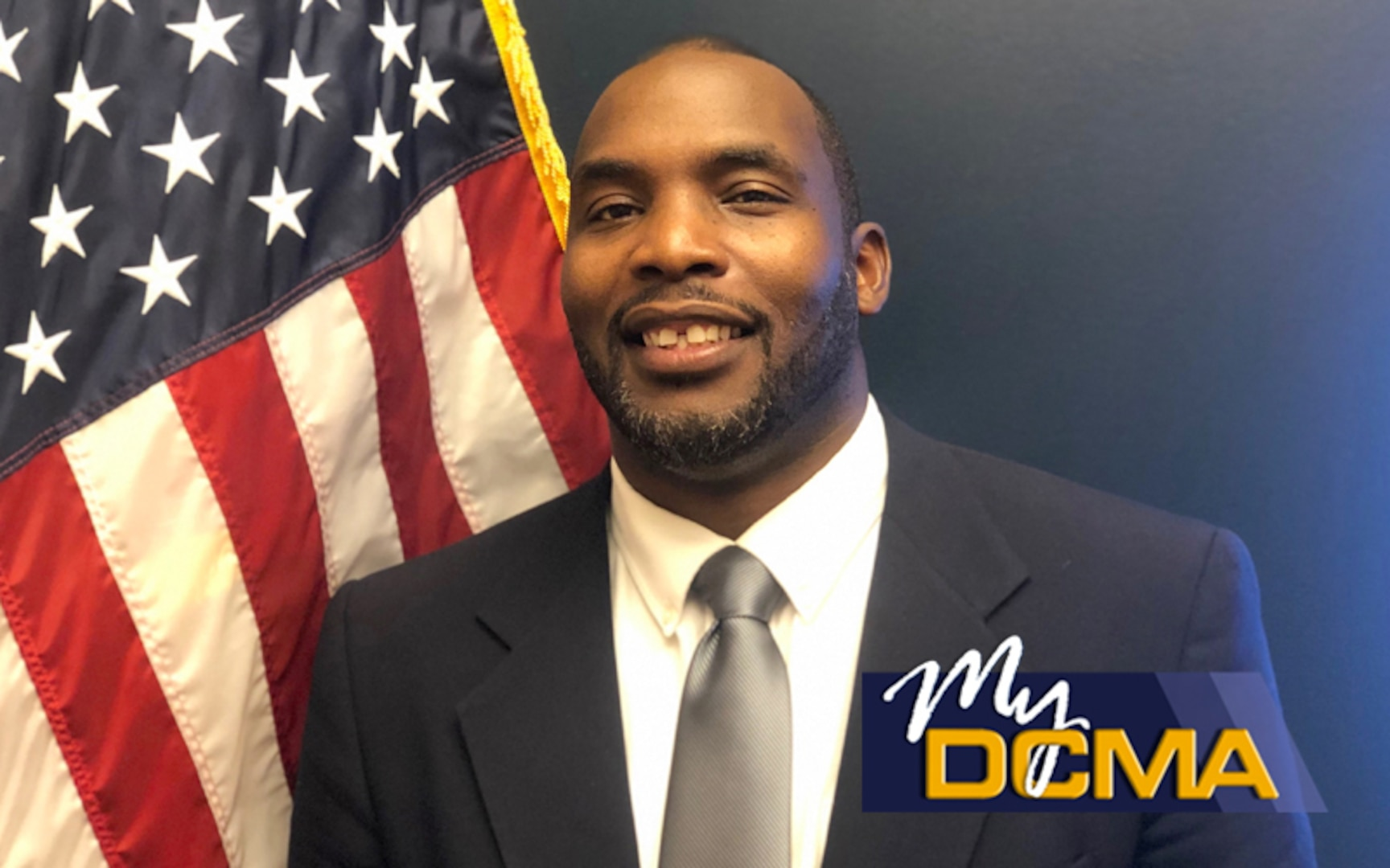Smiling man wearing a navy blue suit stands beside the American flag