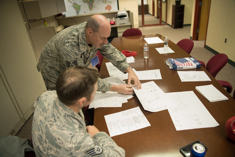 Two Airmen review building plans