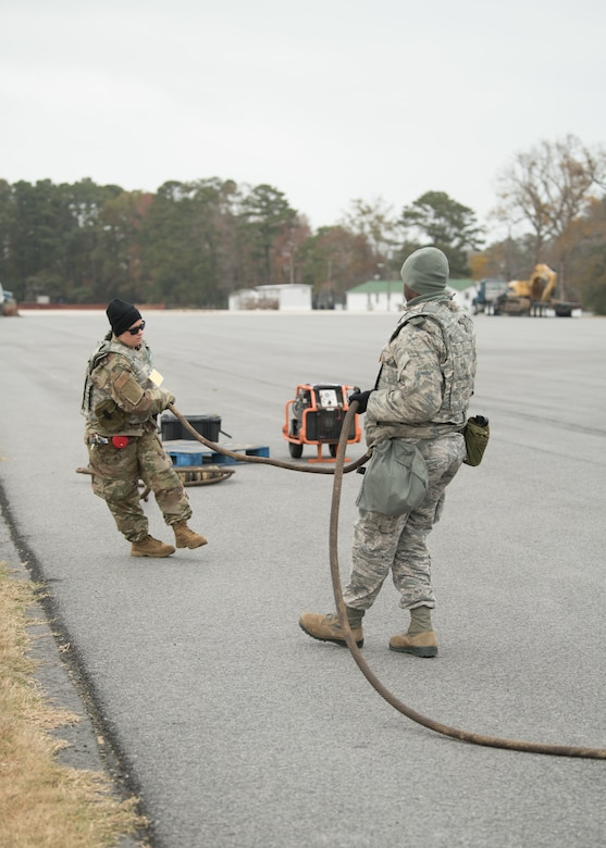 Two Airmen set up a mobile aircraft arrest system