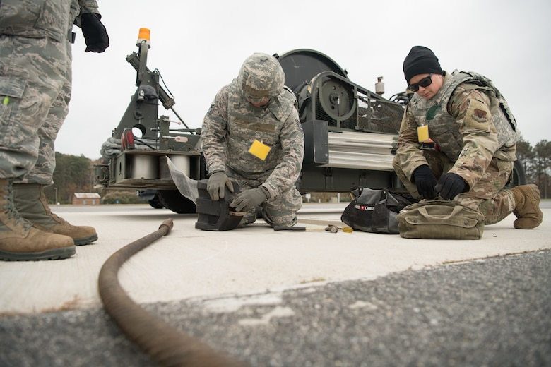 Three Airmen set up a mobile aircraft arrest system