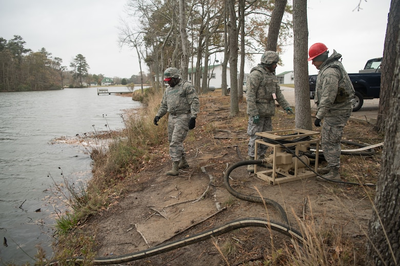 Three Airmen operate a water purification system