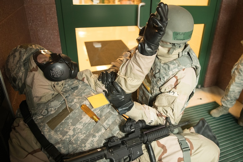 airmen in MOPP gear respond to a simulated medical emergency