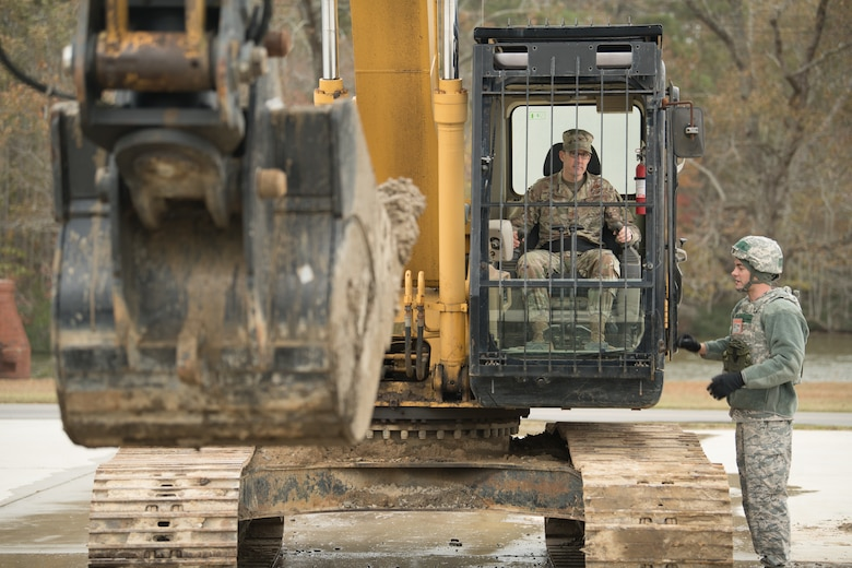 Airmen operate a backhoe