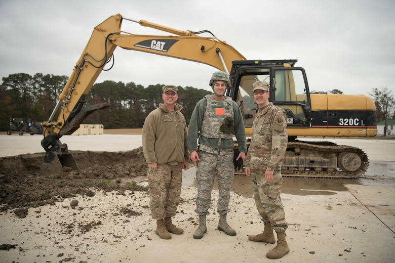 Airmen pose in front of a backhoe