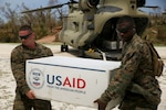 U.S. Marine Lance Cpl. Alex Hurtado and Gunnery Sgt. Damian Henry, a heavy equipment operator and the engineer chief with Special Purpose Marine Air-Ground Task Force - Southern Command, deployed in support of Joint Task Force Matthew, off load supplies for locals affected by Hurricane Matthew at Jeremie, Haiti, Oct. 9, 2016. The Marines delivered bags of rice, cooking oil and other supplies supporting USAID humanitarian and disaster relief assistance in the aftermath of Hurricane Matthew. (U.S. Marine Corps photo by Sgt. Ian Ferro)