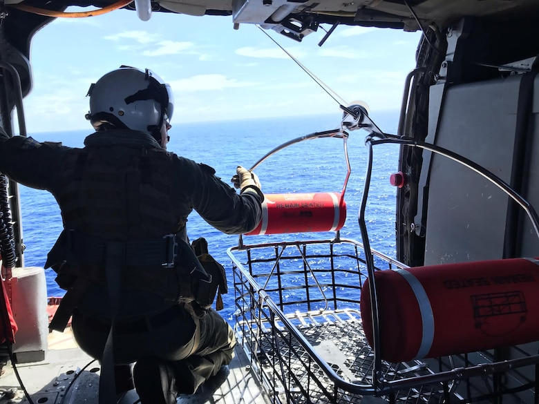 "PACIFIC OCEAN (Nov. 20, 2019) Hospital Corpsman 1st Class Patrick Shea prepares to lower a rescue basket used as part of a medical evacuation mission conducted by the ""Island Knights"" of Helicopter Sea Combat Squadron (HSC) 25. A Chinese national in medical distress aboard the Chinese-flagged vessel Jin Bo was recovered approximately 100 miles northwest of Guam and flown to Guam Memorial Hospital for treatment. HSC-25 provides a multi-mission rotary wing capability for units in the U.S. 7th Fleet area of operations and maintains a Guam-based 24-hour search-and-rescue and medical evacuation capability, directly supporting U.S. Coast Guard and Joint Region Marianas. HSC-25 is the Navy's only forward-deployed MH-60S expeditionary squadron."