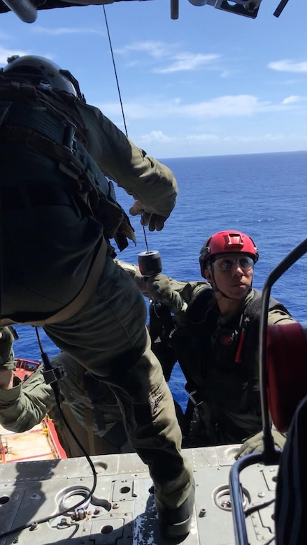 "PACIFIC OCEAN (Nov. 20, 2019) Hospital Corpsman 1st Class Patrick Shea (front) lowers Hospital Corpsman 3rd Class Cody Manning (left) and Naval Air Crewman (Helicopter) 3rd Class Alex Aviles (right) in a rescue basket during a medical evacuation mission conducted by the ""Island Knights"" of Helicopter Sea Combat Squadron (HSC). A Chinese national in medical distress aboard the Chinese-flagged vessel Jin Bo was recovered approximately 100 miles northwest of Guam and flown to Guam Memorial Hospital for treatment. HSC-25 provides a multi-mission rotary wing capability for units in the U.S. 7th Fleet area of operations and maintains a Guam-based 24-hour search-and-rescue and medical evacuation capability, directly supporting U.S. Coast Guard and Joint Region Marianas. HSC-25 is the Navy's only forward-deployed MH-60S expeditionary squadron."