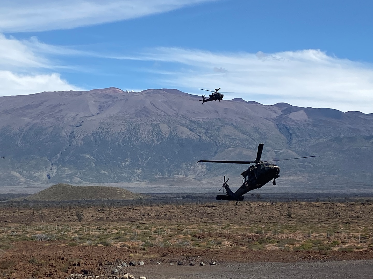 A UH-60 Black Hawk flares before landing with armed escort from an AH-64 Apache during infiltration operations for a Fire Support Coordination Exercise on Pohakuloa Training Area, located on the big island of Hawaii, November 12 through 21, 2019. During the exercise, members of the 25th Air Support Operations Squadron and U.S. Army Pacific 2nd Brigade, 25th Infantry Division, 2nd Brigade Combat Team, integrated with B-52 Stratofortress bombers for live-fire training missions in support of Indo-Pacific Command's Continuous Bomber Presence operations. (Courtesy photo)