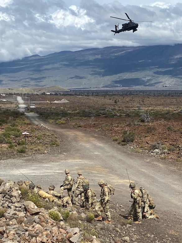 An AH-64 Apache provides armed over watch for Alpha Company during infiltration operations for a Fire Support Coordination Exercise on Pohakuloa Training Area, located on the big island of Hawaii, November 12 through 21, 2019. During the exercise, members of the 25th Air Support Operations Squadron and U.S. Army Pacific 2nd Brigade, 25th Infantry Division, 2nd Brigade Combat Team, integrated with B-52 Stratofortress bombers for live-fire training missions in support of Indo-Pacific Command's Continuous Bomber Presence operations. (Courtesy photo)