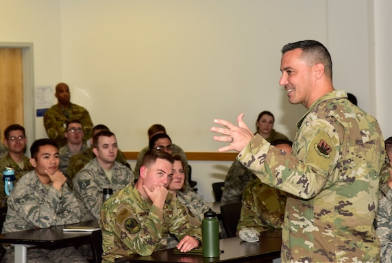 A photo of Chief Master Sgt. Trey Walker, 480th Intelligence, Surveillance and Reconnaissance Wing command chief, talking with Airmen at an NCO all call