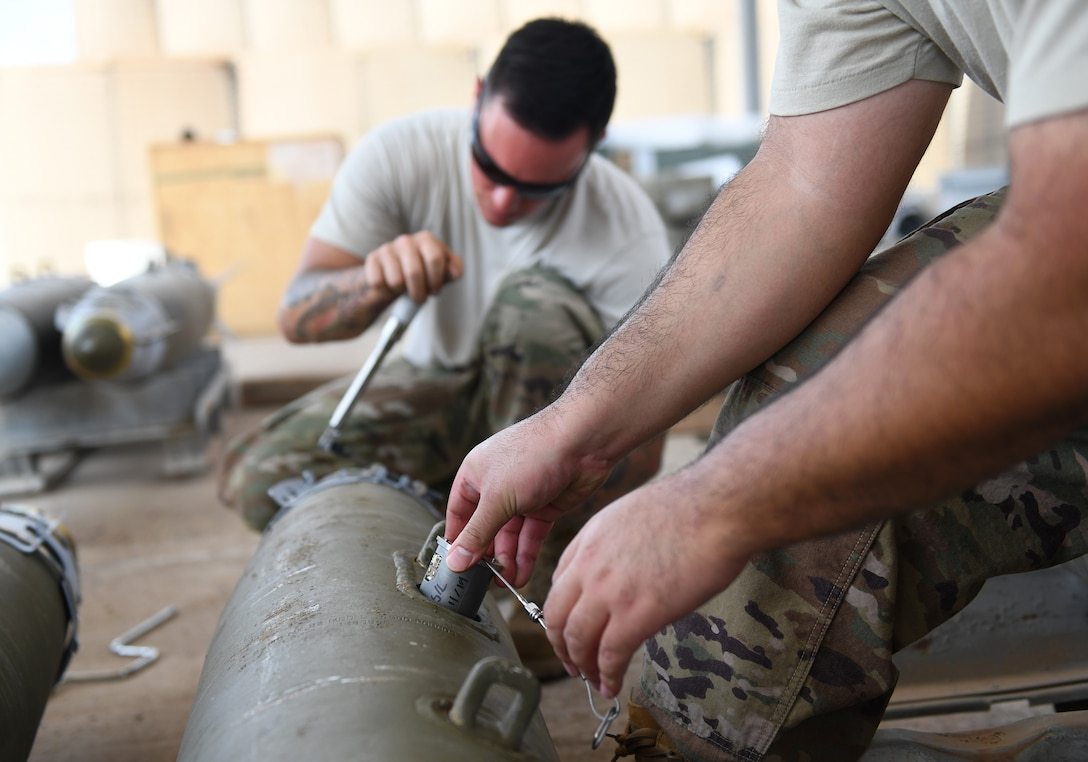 U.S. Air Force munitions Airmen assigned to the 726th Expeditionary Air Base Squadron assemble munitions during a bomb build at Chabelley Airfield, Djibouti, Nov. 12, 2019. The 726th EABS Munitions Systems Airmen build, inspect and store all munitions at the airfield, ensuring mission effectiveness at a moment's notice. (U.S. Air Force photo by Staff Sgt. Alex Fox Echols III)