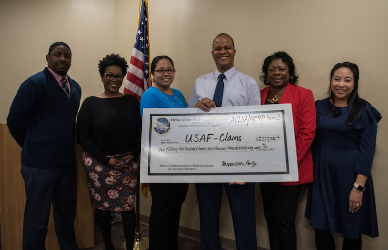 Team members of the Medical Cost Reimbursement Program, hold a check representing the $2.2 million recovered last fiscal year. Each member of the team handles over 560 cases each year. (U.S. Air Force photo by Airman 1st Class Sarah Dowe)