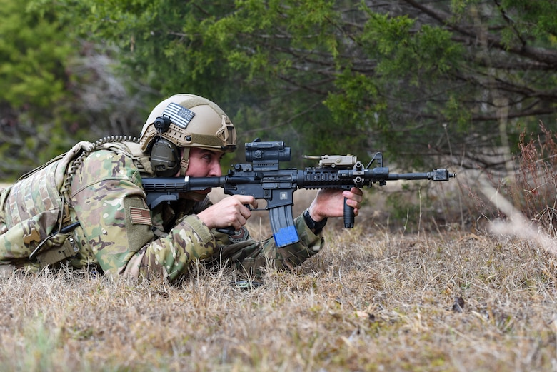 An Airman lays in the prone position with an M4 rifle