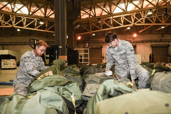 U.S. Air Force Senior Airman Santia Baker, left, and Senior Airman Ronald Tedder, 39th Logistics Readiness Squadron individual protective equipment specialists, sift through mobility bags Nov. 18, 2019, at Incirlik Air Base, Turkey. Because of the hazardous nature of some Air Force missions, IPE Airmen are responsible for providing life-saving gear to members across their installation. (U.S. Air Force photo by Staff Sgt. Joshua Magbanua)