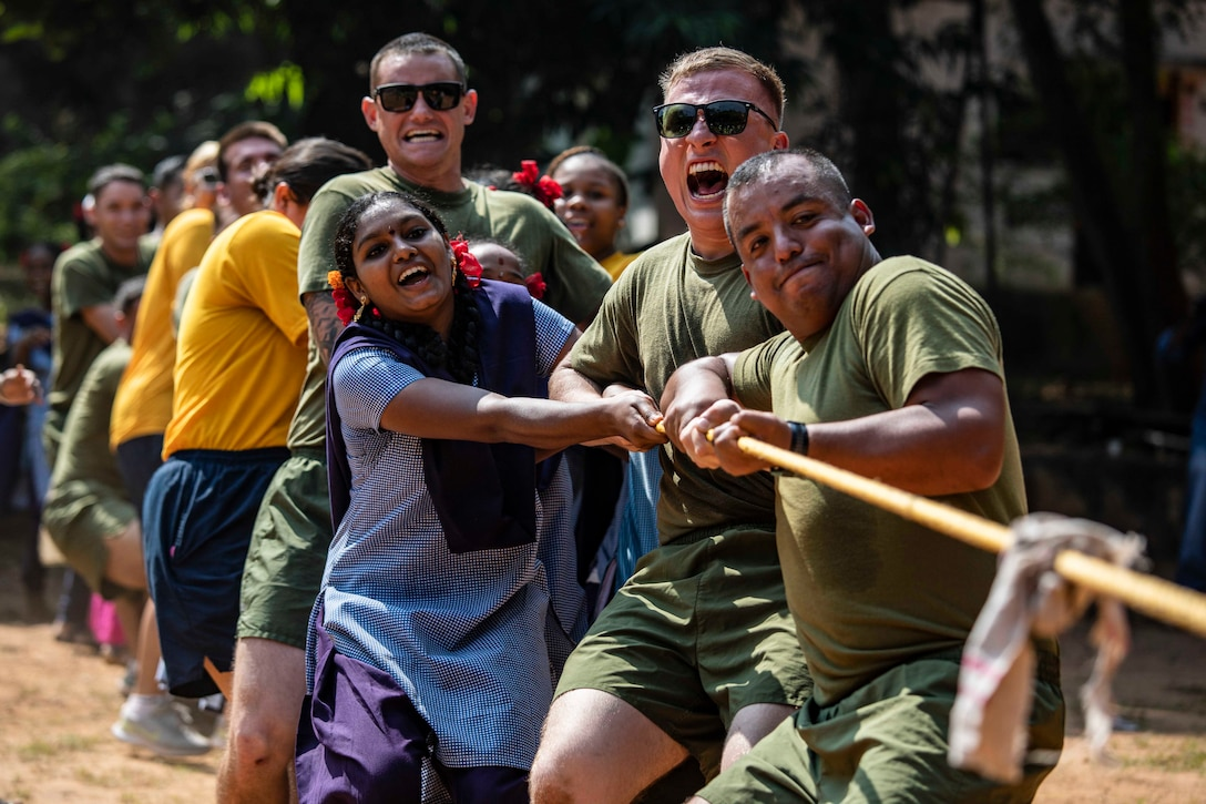A group of Marines and sailors pull on a rope with children.