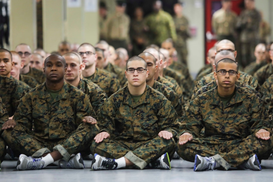 A group of Marines sit on the floor side by side.