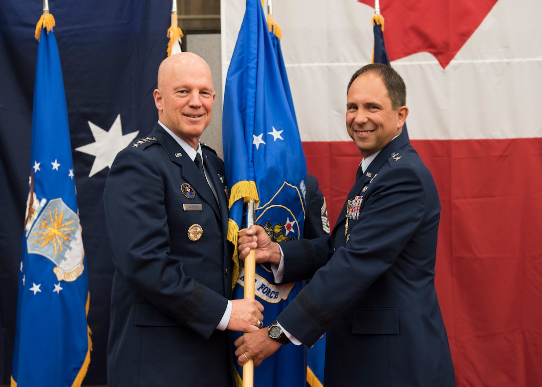 "Gen. John W. ""Jay"" Raymond, U.S. Space Command and Air Force Space Command commander, presents the 14th Air Force guidon to Maj. Gen. John. E. Shaw, Combined Force Space Component Command and 14th AF commander, during a change of commander ceremony Nov. 20, 2019, at Vandenberg Air Force Base, Calif. As the Air Force's sole numbered Air Force for space, 14th AF is responsible for the organization, training, equipping, command and control and employment of Air Force space forces to support operational plans and missions for U.S. combatant commanders and air component commanders. (U.S. Air Force photo by Airman 1st Class Aubree Milks)"