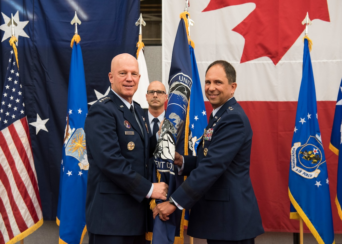 """Gen. John W. """"Jay"""" Raymond, U.S. Space Command and Air Force Space Command commander, presents the Combined Force Space Component Command guidon to Maj. Gen. John. E. Shaw, CFSCC and 14th AF commander, during a change of commander ceremony Nov. 20, 2019, at Vandenberg Air Force Base, Calif. The CFSCC mission is to plan, integrate, conduct, and assess global space operations in order to deliver combat relevant space capabilities to Combatant Commanders, Coalition partners, the Joint Force, and the Nation. (U.S. Air Force photo by Airman 1st Class Aubree Milks)"""