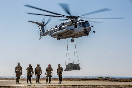 U.S. Marines with Landing Support Company, 1st Transportation Battalion, prepare to detach pallets off a helicopter.