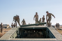 U.S. Marines with Bridge Company, 7th Engineer Support Battalion work with the Royal Marines to build a bridge.