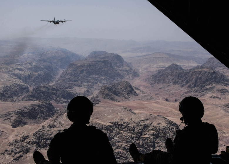 Two loadmasters from the 700th Airlift Squadron scan out of the rear of a C-130H3 while flying over Jordan during Exercise Eager Lion. (Senior Airman Josh Kincaid)