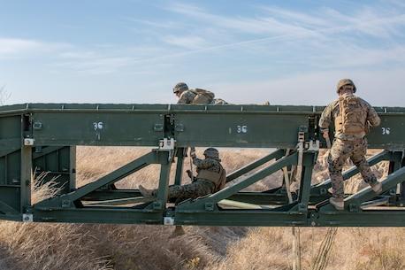 U.S. Marines with Bridge Company, 7th Engineer Support Battalion, build a medium-girder bridge.