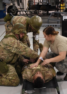 Airmen with the 442d Maintenance Squadron provide self-aid buddy care to a simulated-wounded wingman during a wing-level exercise, Ozark Thunder 20-01, at Whiteman Air Force Base, Mo., Nov. 3, 2019. The exercise is meant to test the wing's ability to survive and operate and perform mission essential tasks during contingency operations.