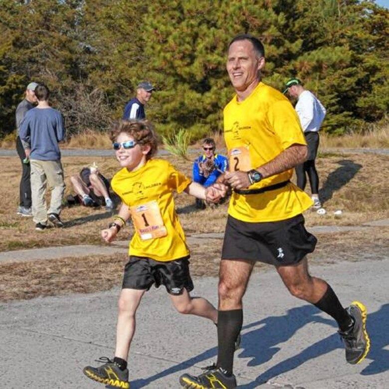 Lt. Col. (Dr.) Daniel Toocheck runs a marathon with his son, Nikolas.