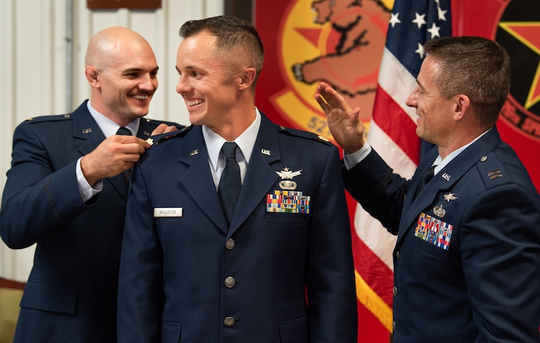 Maj. Scott Hollister's brothers, Taylor (left) and Ryan (right) pin on his new rank during Scott's promotion ceremony in September. (Staff Sgt. Laura Turner)