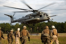 U.S. Marines with the Basic Landing Support Specialist Course, Logistics Operations School, Marine Corps Combat Service Support Schools, move away after attaching a beam to a CH-53E Super Stallion during a helicopter support team training exercise at the Condor range on Camp Lejeune, N.C., Nov. 5, 2019. HST missions consist of hooking external loads of gear and supplies to aircraft, allowing them to deliver and recover them quickly and efficiently. (U.S. Marine Corps photo by Lance Cpl. Taylor Smith)