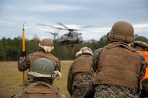 U.S. Marines with the Basic Landing Support Specialist Course, Logistics Operations School, Marine Corps Combat Service Support Schools, prepare to attach a beam to a CH-53E Super Stallion during a helicopter support team training exercise at the Condor range on Camp Lejeune, N.C., Nov. 5, 2019. HST missions consist of hooking external loads of gear and supplies to aircraft, allowing them to deliver and recover them quickly and efficiently. (U.S. Marine Corps photo by Lance Cpl. Taylor Smith)